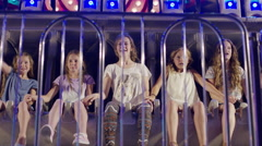 Low angle slow motion medium shot of girls sitting on amusement park ride / Stock Footage