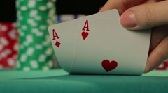 Closeup of poker player's hand checking cards, holding two aces, chance to win - stock footage