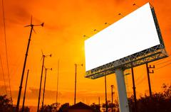 Blank billboard  with wind turbine at sunset time for advertisement Stock Photos