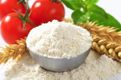 Bowl of finely ground flour, wheat ears and fresh tomatoes - still life - stock photo