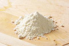 Pile of wheat flour on wooden rolling board - stock photo