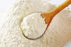 Pile of finely ground flour and wooden spoon - stock photo