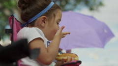 Low angle slow motion shot of girl eating pastry / American Fork, Utah, United Stock Footage