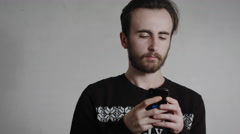 Young Handsome Man With A Beard Typing Massage With Phone On A White Background Stock Footage