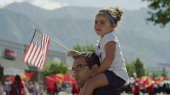 Medium slow motion shot of girl waving American flag at parade / American Fork, Stock Footage