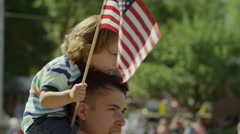 Medium slow motion shot of boy waving American flag at parade / American Fork, Arkistovideo
