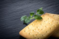 dry salted crackers on granite plate with oregano - stock photo