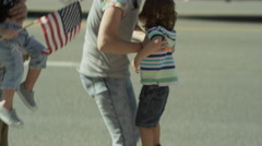 Medium slow motion shot of family watching parade / American Fork, Utah, United Stock Footage
