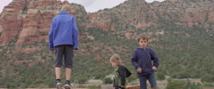 Slow Motion Three Children Playing in the Rocky Desert Stock Footage