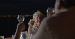 People clinking glasses of wine while sitting at table - stock footage