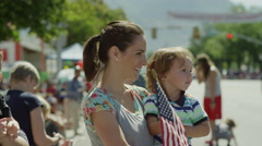 Medium slow motion shot of family watching parade / American Fork, Utah, United Stock Footage