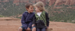 Slow Motion Little Kids Kiss Each Other Sitting on a Rock in a Desert Area Stock Footage