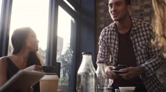 4K Happy group of friends chatting & using technology in city coffee shop Stock Footage