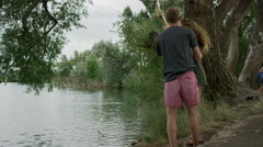 Wide slow motion panning shot of couple playing at lake / Mona, Utah, United Stock Footage