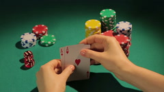 Fortunate poker player checking cards, getting chance to win game with two aces - stock footage