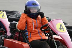 Girl is driving Go-kart car with speed in a playground racing track. Stock Photos