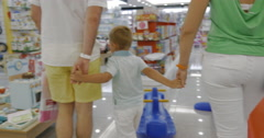 Child is attracted with toy cooker in supermarket - stock footage