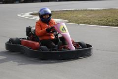 girl is driving Go-kart car with speed in a playground racing track. - stock photo