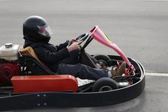 boy is driving Go-kart car with speed in a playground racing track. - stock photo