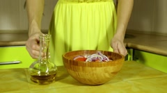 Woman pours salad oil. Female hands watering vegetables oil - stock footage