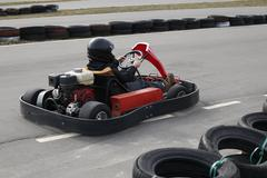 Boy is driving Go-kart car with speed in a playground racing track. Stock Photos