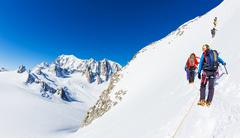 a group of mountaineer climb a snowy peak. - stock photo