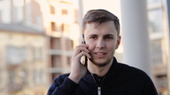 Young handsome man communicating over the telephone in the street - stock footage
