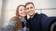 Beautiful couple in love making selfies smiling on camera of their cellphone Stock Footage