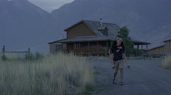 Wide panning shot of man carrying girlfriend piggyback / Mona, Utah, United Stock Footage