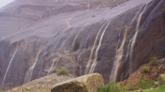 Medium shot of waterfall over rocky cliff / Lake Powell, Utah, United States Stock Footage