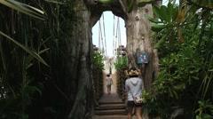 People walk by the suspension bridge at Sentosa island, Singapore. Stock Footage