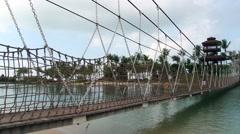Person walks walk by the suspension bridge at Sentosa island, Singapore. Stock Footage