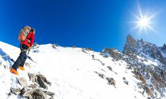 Mountaineer climbs a snowy peak. In background the famous peak Dent du Geant - stock photo