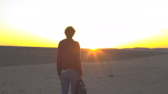 Young hippie man gazes at sun setting in desert - stock footage
