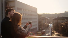 Happy couple resting on the balcony, girl taking pictures of the city Stock Footage