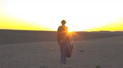 Young guy with guitar walks towards sunset in desert Stock Footage