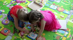 Little girls age five playing on children's rug folded mosaic of cartoon Stock Footage