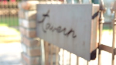 Rack Focus Tavern Sign on a Wrought Iron Fence Stock Footage