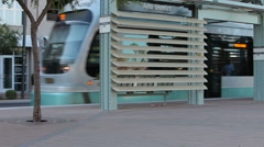 Light Rail Train Cruises by Stop Downtown Stock Footage