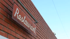Restaurant Sign Shakes in the Wind on a Clear Day Stock Footage