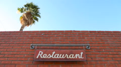 Palm Tree Towers Over a Restaurant as a Sign Swings Stock Footage