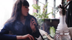 Beautiful young woman inhaling hookah. girl smoking shisha in cafe Stock Footage