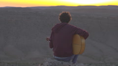 Young hippie playing guitar in desert sunset - stock footage