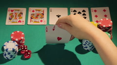 Poker player catching full house hand, checking cards before betting chips - stock footage