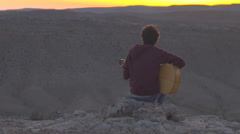 Hippie peacefully playing guitar on a desert cliff at sunset - stock footage