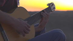 Close Up - hands playing and strumming on guitar in desert sunset - stock footage