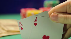 Person enjoying successful poker game with pair of aces, betting cash and chips - stock footage