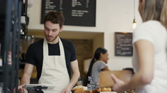 4K Cheerful worker serving customers & taking payment in city coffee shop Stock Footage