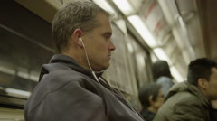 Medium low angle shot of man using cell phone on subway / New York, New York, Stock Footage