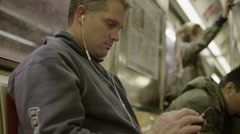 Medium shot of man using cell phone on subway / New York, New York, United Stock Footage